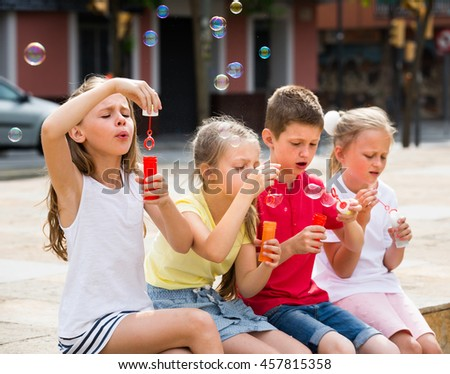 happy boy and his little girlfriends in elementary school age blowing bubbles outdoors - stock photo