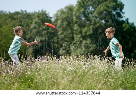 Happy boy and little girl playing frisbee on a meadow in a sunny day - stock photo
