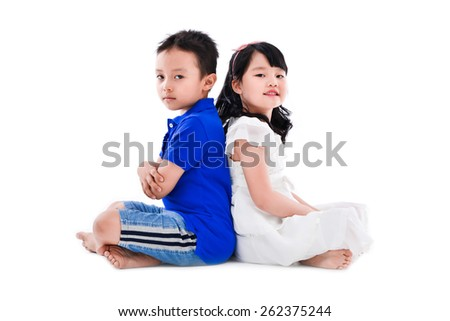 Happy boy and little girl sitting back to back - stock photo