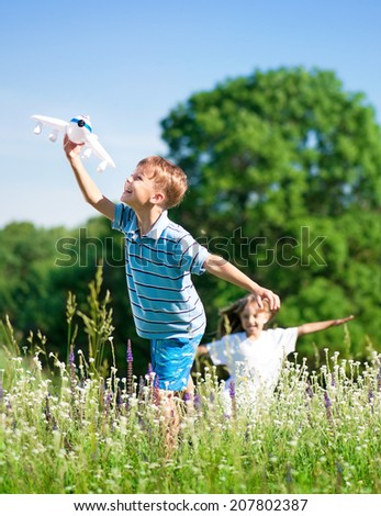 Happy boy and little girl with plane on a meadow in a sunny day