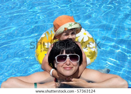 happy boy and mom in the swimming pool, leisure - stock photo