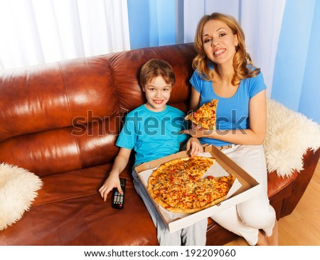Happy boy and mother eating pizza on the couch - stock photo