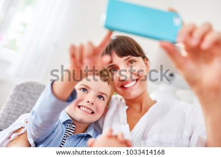 Happy boy and mother take a selfie with the camera cell phone