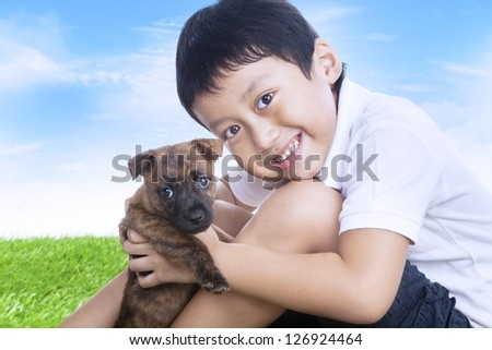Happy boy and puppy outdoors under blue sky