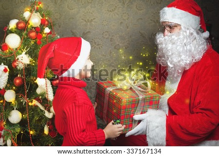 Happy boy and Santa Claus with big gift or present box! Child dressed in red Santa hat. Xmas and New Year holiday!