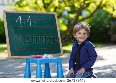 Happy boy at blackboard practicing mathematics, outdoors. Back to school concept. - stock photo