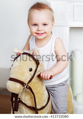 happy boy   at home with a toy horse - stock photo