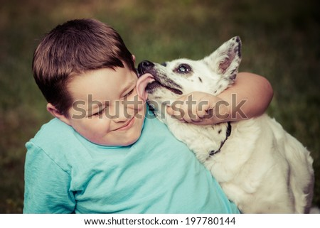 Happy boy being licked by his pet dog in image with vintage filter  - stock photo
