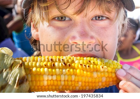 Happy boy eating corn on the cob - stock photo