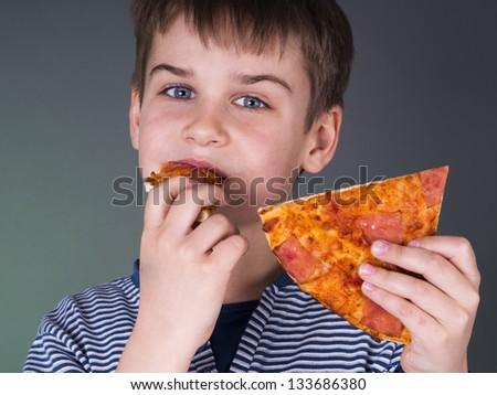 Happy boy eating pizza - stock photo