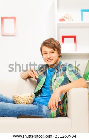 Happy boy eating popcorn while sitting on sofa - stock photo