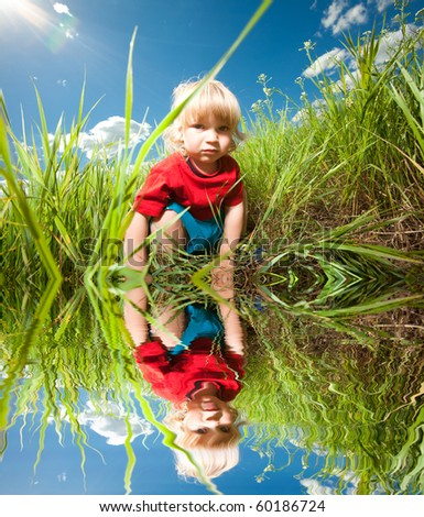 Happy boy enjoy on the meadow. Specular reflection in water - stock photo