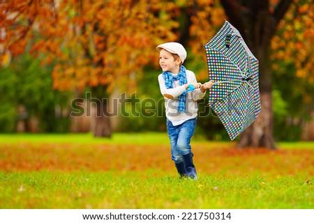happy boy enjoying an autumn rain in park - stock photo