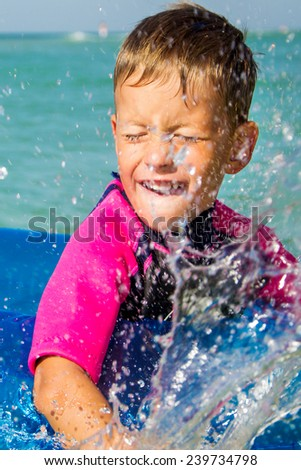 happy boy enjoying swimming in sea with rubber ring - stock photo