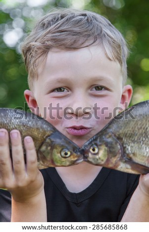 Happy boy fisherman holding two fish bream caught at the bait - stock photo