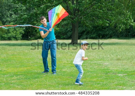 Happy Boy Flying The Colorful Kite With His Father In The Park