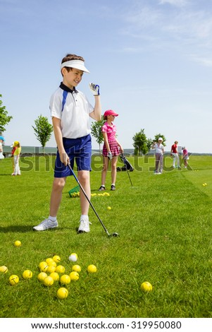 Happy boy golf player practicing in golf school  - stock photo