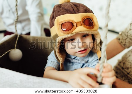 Happy boy having fun in handmade basket of air balloon. Child play at home with parents. Young pilot indoors. Boy in hat like a helmet and bowtie looking away. - stock photo