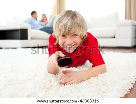Happy boy holding a remote lying on the floor in the living-room - stock photo