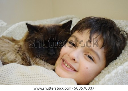 Happy boy holding his pet cat