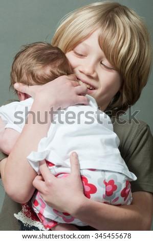 Happy boy holding new born baby - stock photo