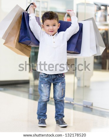 Happy boy holding shopping bags at the mall - stock photo