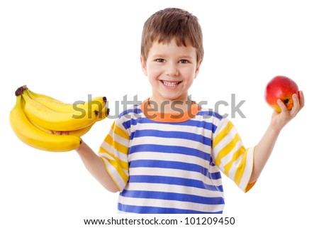 Happy boy holds a bunch of bananas and red apple, isolated on white