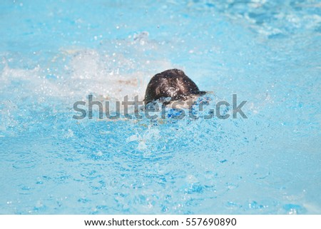 Happy boy in a swimming pool. Cute little kid boy having fun in a swimming pool. Outdoors. Sport activities for children.