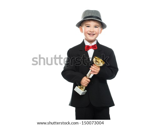 Happy boy in black suit holding prize cup - stock photo