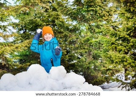 Happy boy in blue winter jacket playing snowballs - stock photo
