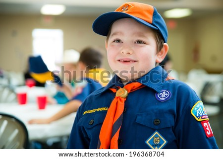 Happy boy in Cub Scout uniform at annual awards banquet in candid image - stock photo