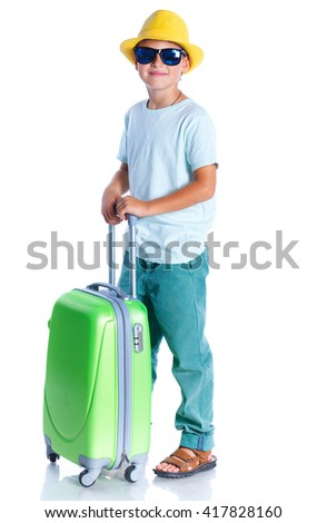 Happy boy in hat and sunglasses traveling with suitcase. Isolated on the white background