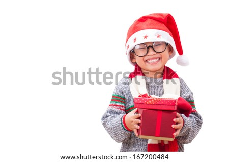 Happy boy in Santa red hat holding Christmas gift and wearing glasses. Christmas concept.  - stock photo