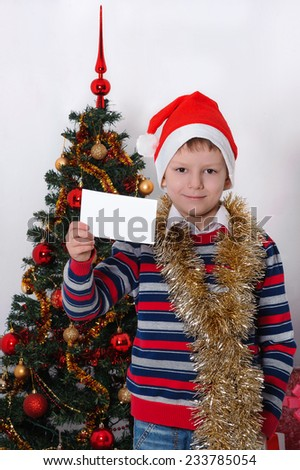 Happy boy in Santa red hat holding Christmas greeting blank card in hands. Christmas concept. - stock photo