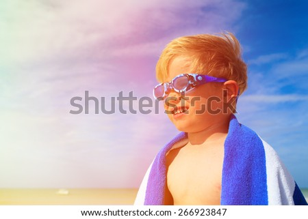 happy boy in swimming goggles on summer sea beach