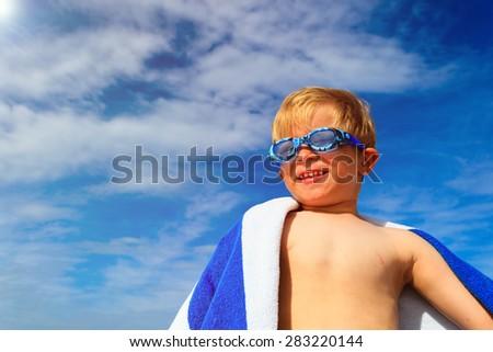 happy boy in swimming goggles on summer sea beach - stock photo