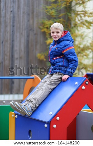 Happy boy in warm blue bright coat having fun at the playground sitting on top of the wooden house on a winter, late autumn or early spring day - stock photo