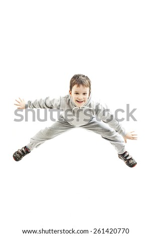 Happy boy is jumping at studio. Isolated on white background  - stock photo