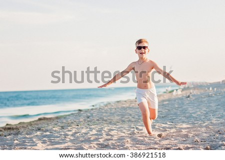 Happy boy is running along the sea