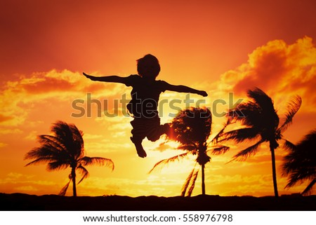 happy boy jumping at sunset beach