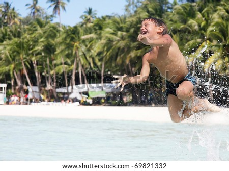 happy boy jumping in water