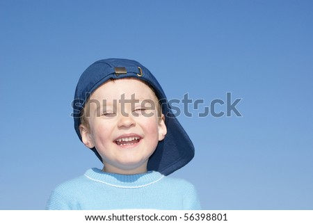 Happy boy laughs, in a baseball cap, background sky