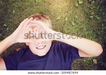 Happy boy laying outdoors  making a heart shape with his hands - stock photo