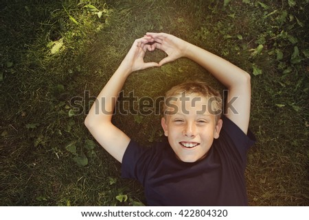 Happy boy laying outdoors  making a heart shape with his hands