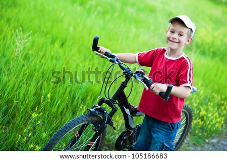happy boy leads his bike on a footpath