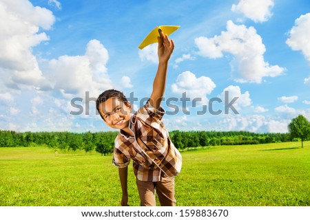 Happy boy leaning and throwing yellow paper airplane on bright sunny day in the field - stock photo