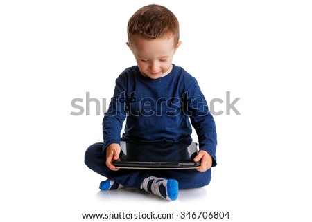 Happy boy looking and playing with a tablet in a meditation posture, isolated on white - stock photo