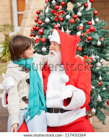 Happy boy looking at Santa Claus while sitting in front of decorated Christmas tree - stock photo