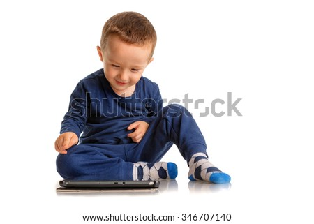 Happy boy looking, playing and pointing at a tablet in a relaxed posture, isolated on white - stock photo