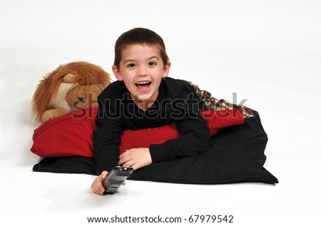 happy boy lounging on pillows on the floor, watching television with remote control in hand. - stock photo